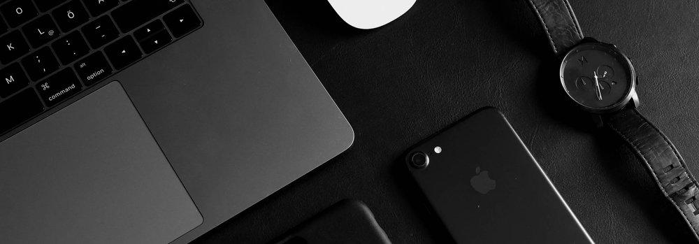 Macbook, iPhone und Uhr in schwarz