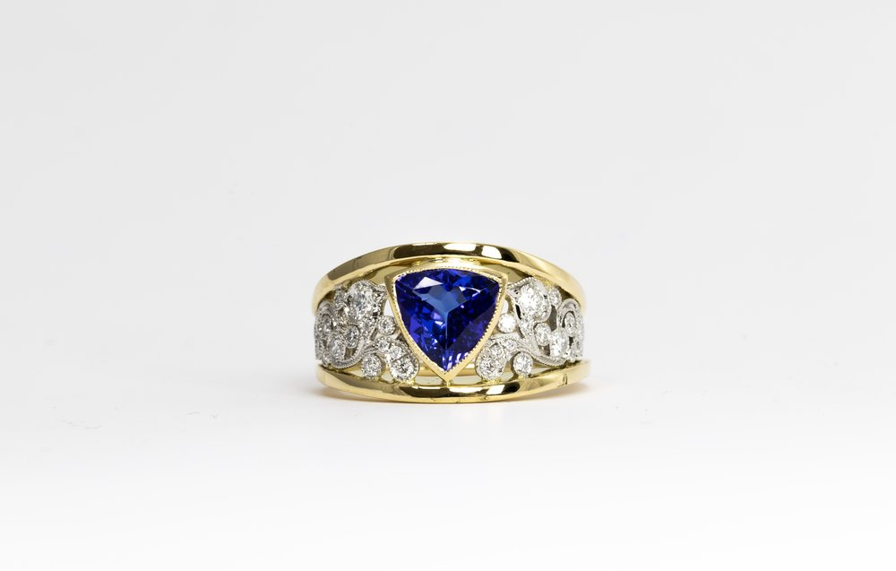 Tanzanite and Diamond Ring. The trilliant cut tanzanite is 1.62ct and has been rubover set in yellow gold and on either side, platinum, diamond set, foliate scrollwork. 18ct yellow raised edges. Made in Chichester, England.