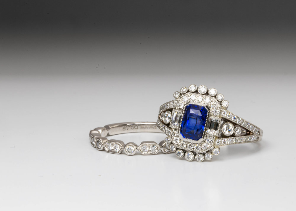 Sapphire and diamond Edwardian Style Cluster Ring. The central rectangular faceted sapphire is 1.58ct and is rub over set with a millegrain edge, on either side are 2 baguette diamonds, surrounded by further round brilliant cut diamonds, including on the split shoulders. 2 round brilliant cut diamonds are set inside the split shoulders on either side, all set with a millegrain edge. Total diamond weight is 0.61ct graded for colour and clarity as G, VS/SI respectively. Hallmarked 950 for platinum, with the Chichester Cross mark . Total gross weight is 7.9g Made in Chichester, England.