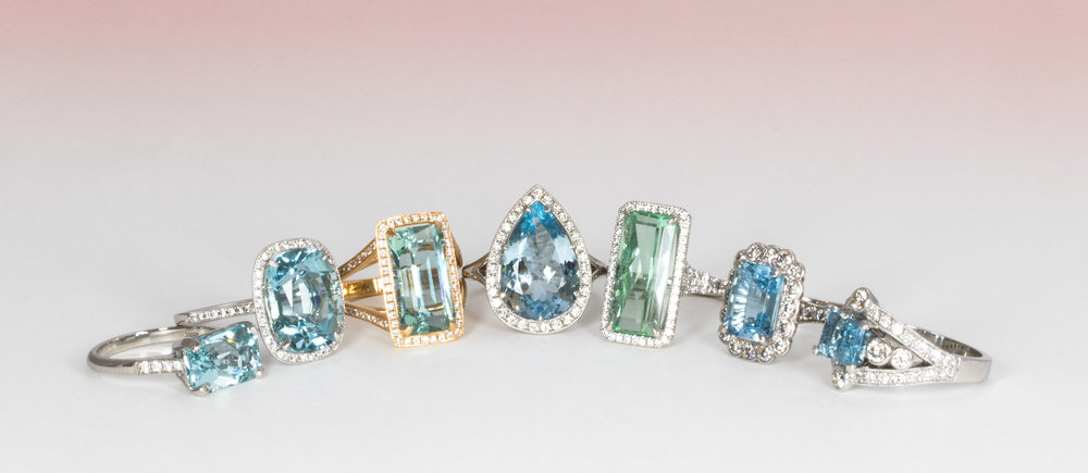 A selection of Bespoke Aquamarine and diamond rings in various shades of blue.