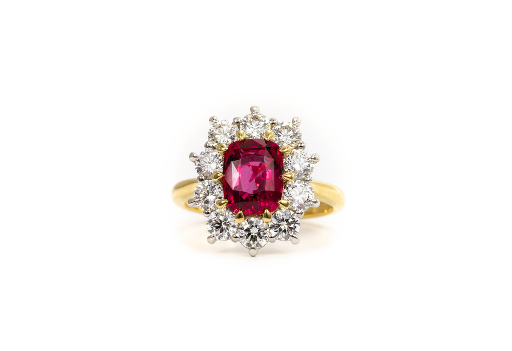 The central faceted oval cushion cut ruby 2.54ct and is claw set in 18ct yellow gold, the surrounding 10 round brilliant cut diamonds are claw set in platinum, total diamond weight is 1.67ct.