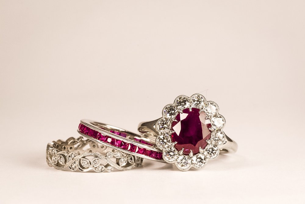 Ruby and Diamond Cluster Ring. The oval faceted Burmese ruby is 3.03ct and has been set in 12 fine, talon style claws and surrounded with a rubover set cluster of 12 modern round brilliant cut diamond with a combined weight of 1.04ct, graded for colour and clarity as G/H and VS1/2 respectively. Ruby certificated by The Gem and Pearl Laboratory, report number 13969. Hallmarked 950, Platinum and with the Chichester Cross mark.