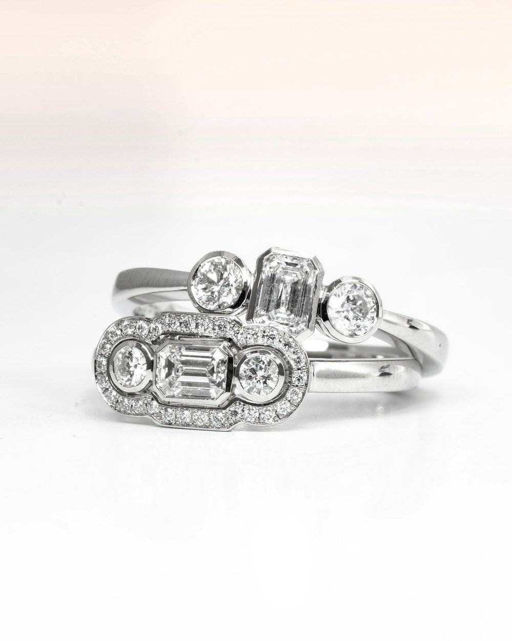 Two platinum mounted emerald cut and round cut diamond set rings. Made in Chichester, England.