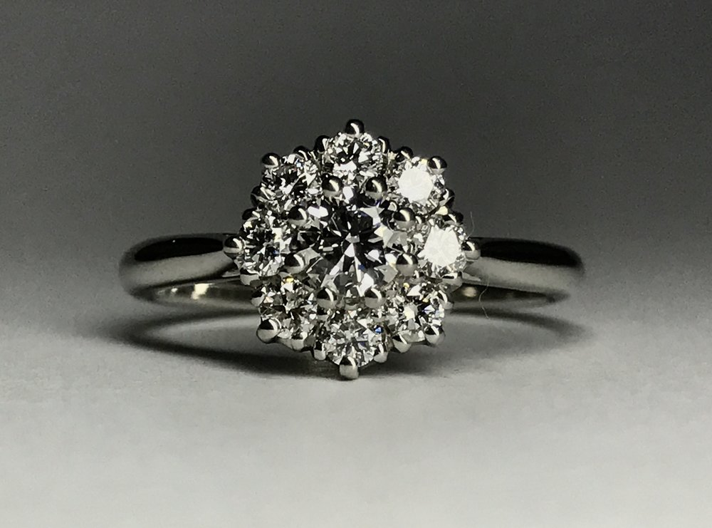 A classic 9 stone coronet cluster ring, this one has a modern twist as it has space for a wedding ring to fit underneath. Made in Chichester, England.