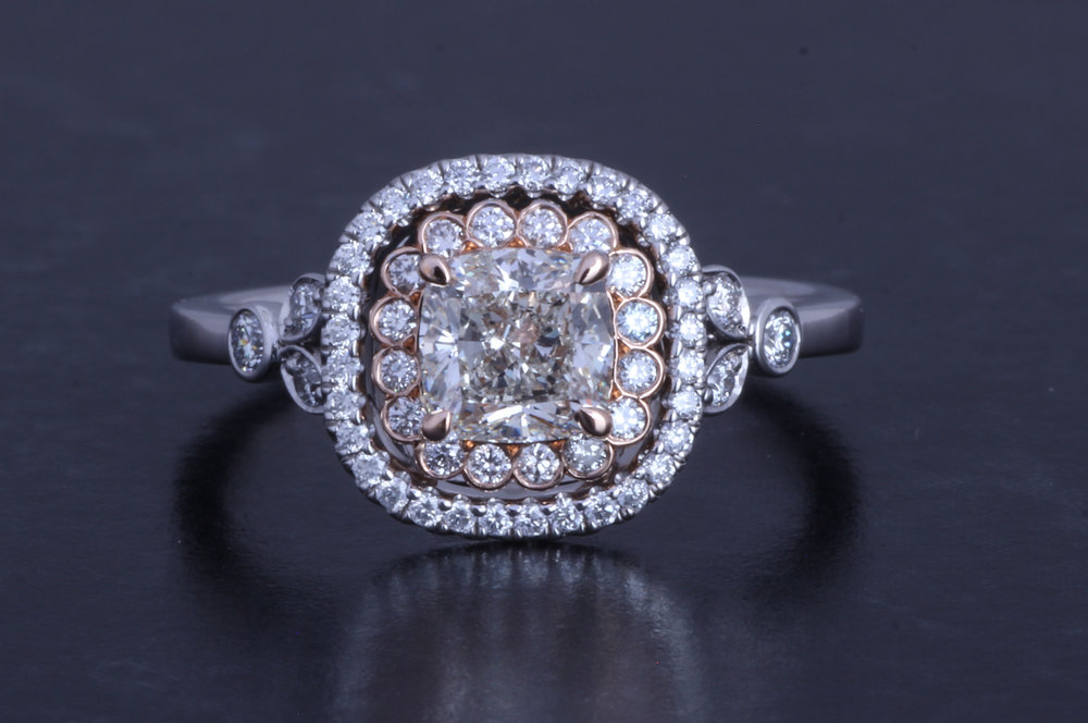Platinum and rose gold mounted cushion cut and round cut diamond cluster ring. Made in Chichester, England.