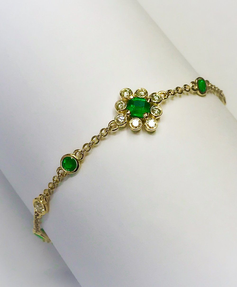 A bespoke commission, alternating Diamond and Emerald rub over set bracelet with feature Emerald and Diamond floral cluster set equal distance apart. Made in Chichester, England.