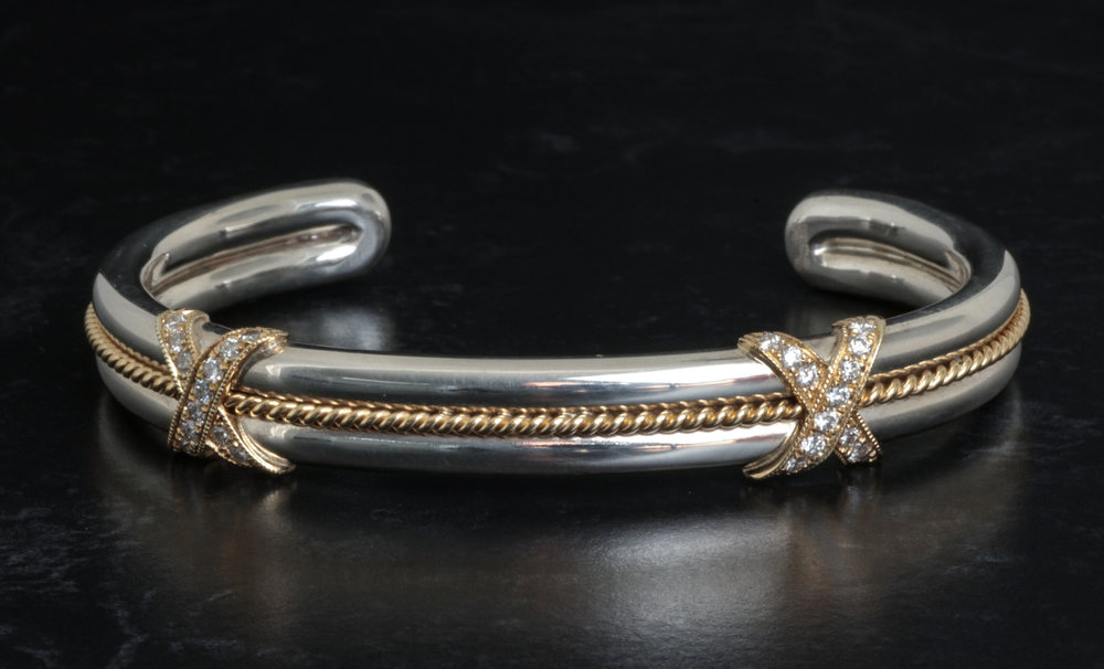Silver and gold twist torque bangle with diamond set kiss decoration. Made in Chichester, England.
