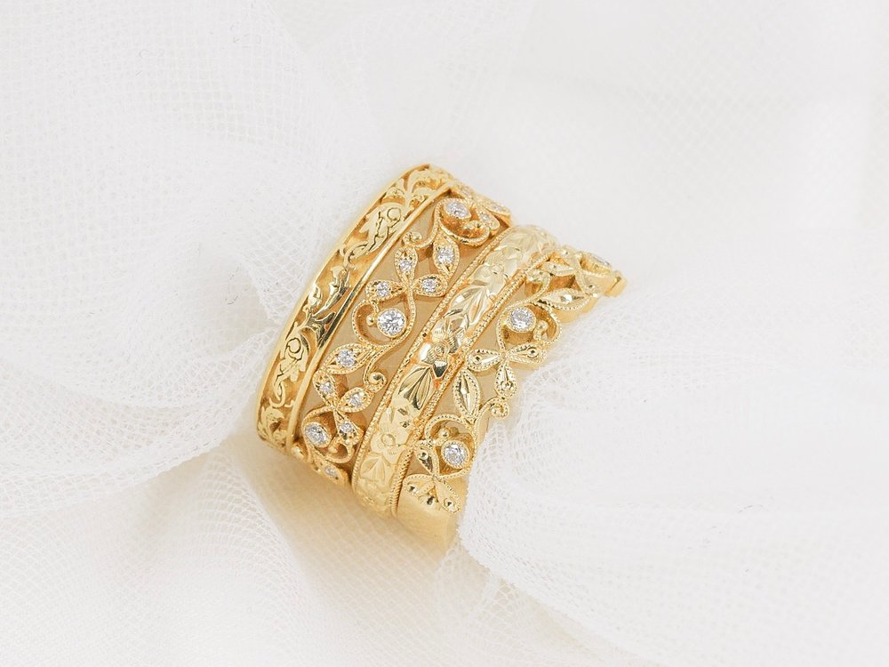 A selection of yellow gold engraved and diamond set foliate wedding rings.
