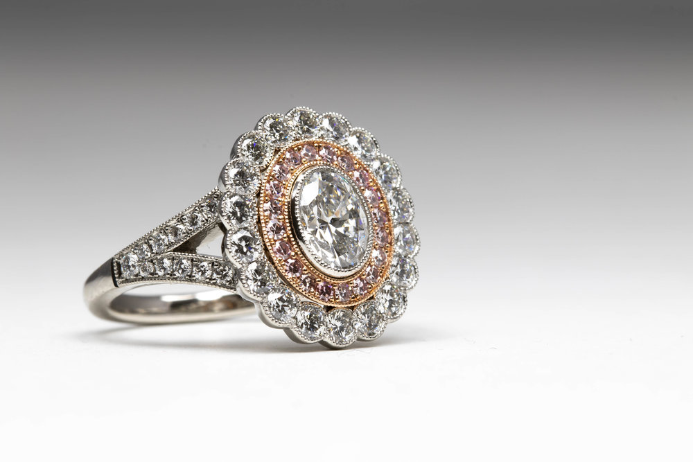 D colour centre oval diamond with natural pink diamond surround. Made in Chichester, England.