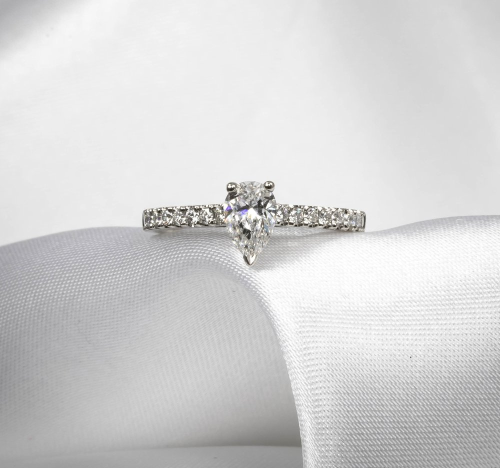Platinum mounted claw set pear shaped diamond with diamond set shoulders. Made in Chichester, England.