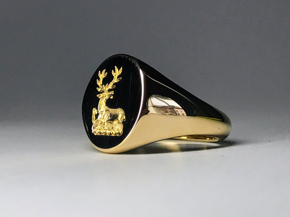 Traditional oval signet ring seal engraved by hand with a family crest.