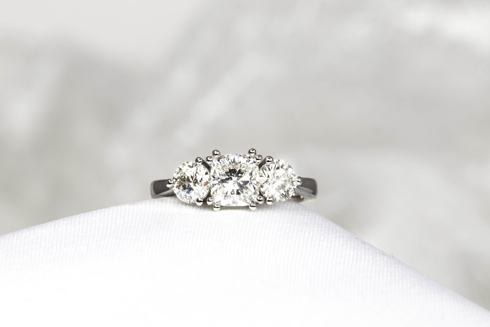 A platinum mounted claw set cushion cut diamond with round diamonds either side. Made in Chichester, England.