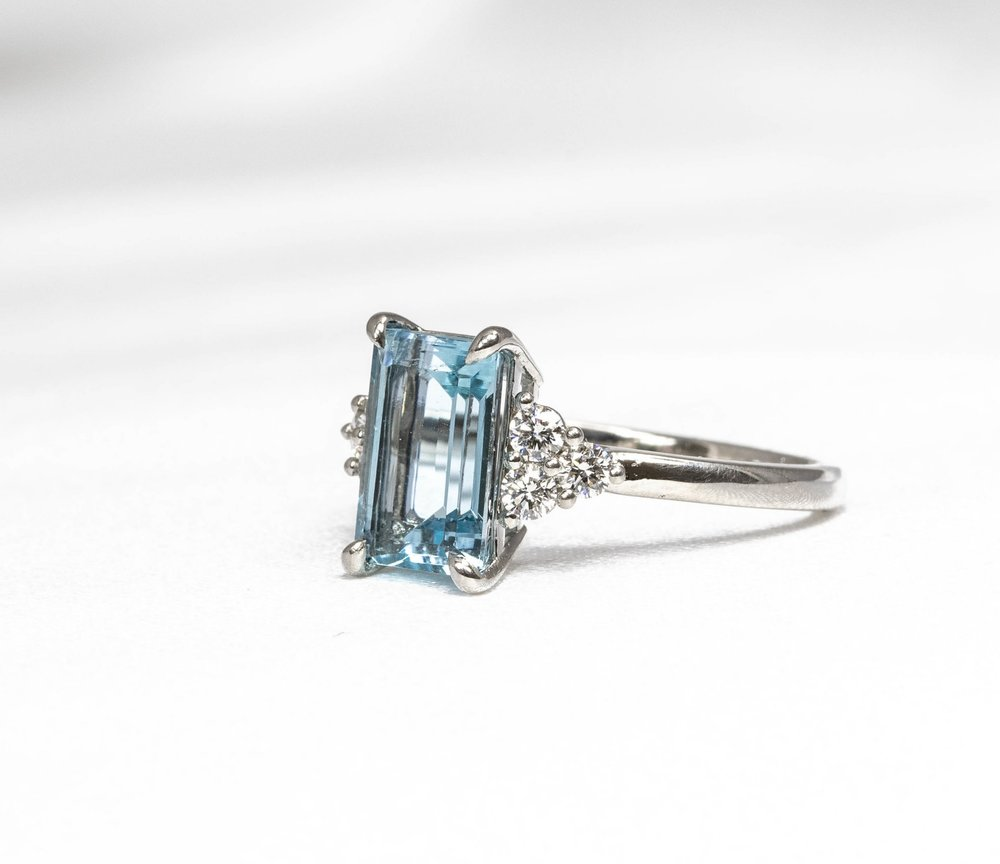 Emerald cut aquamarine with trefoil diamond set shoulders. Made in Chichester, England.