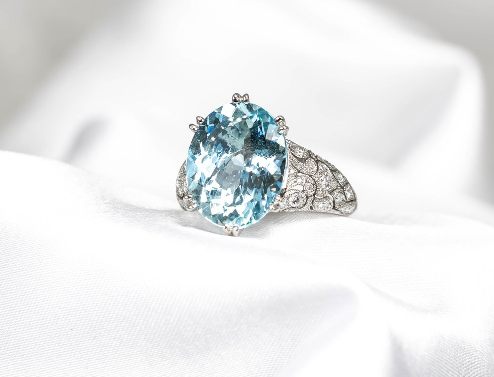 Oval aquamarine with diamond set fine scrollwork shoulders. Made in Chichester, England.