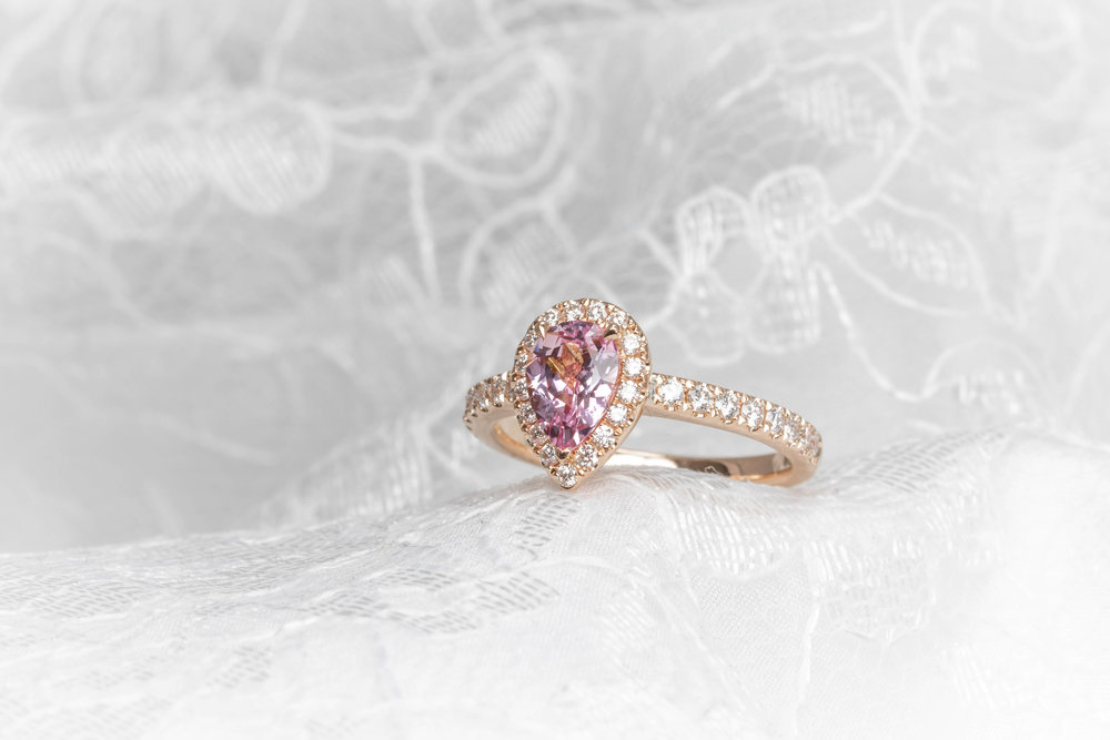 18ct rose gold mounted, pale pink, pear-shaped sapphire with diamond surround and diamond set shoulders. Made in Chichester, England.