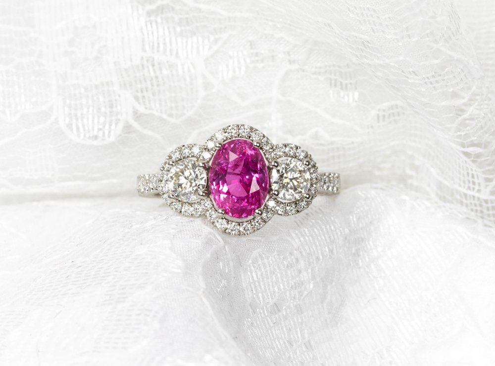 Platinum mounted, vivid pink oval sapphire and diamond triple cluster ring. Made in Chichester, England.