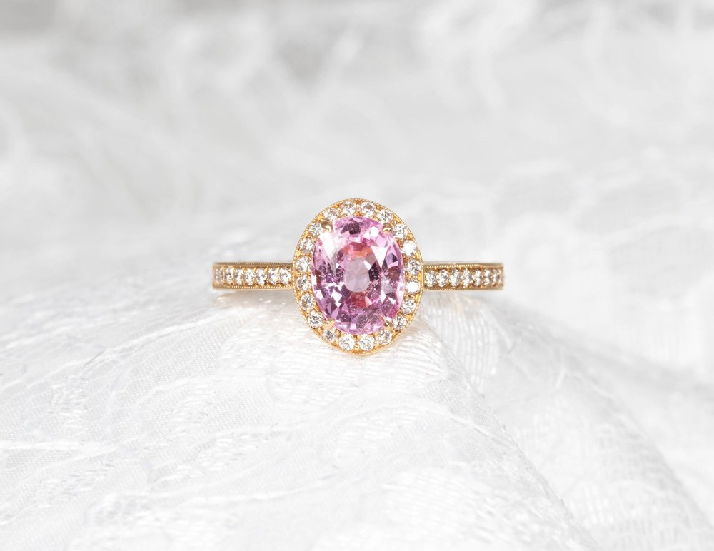 18ct rose gold mounted oval pale pink sapphire and diamond cluster. The centre sapphire being claw set and the diamonds grain set with millegrain edge decoration.