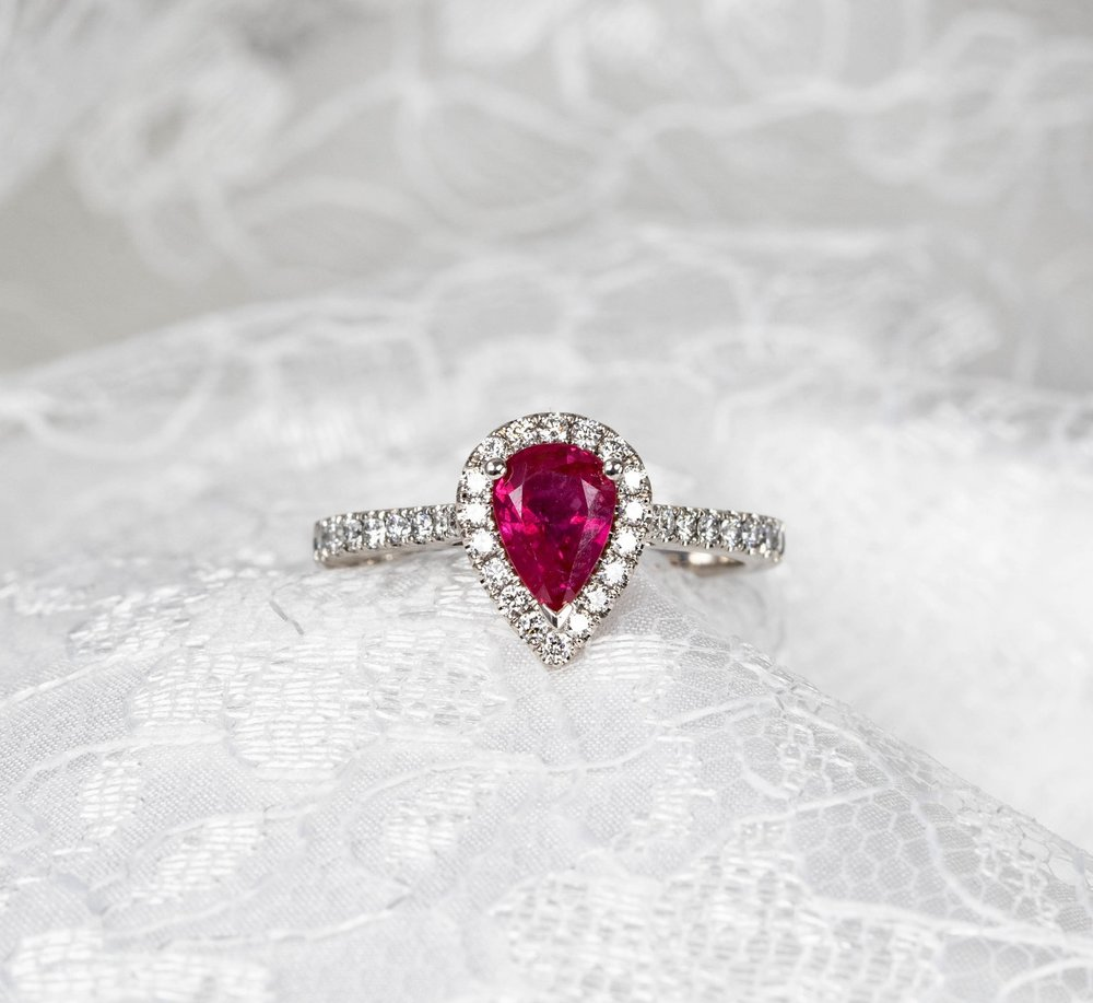 Platinum mounted pear shaped ruby and diamond cluster ring with claw setting for the ruby and cut-away setting for the diamonds. Made in Chichester, England.