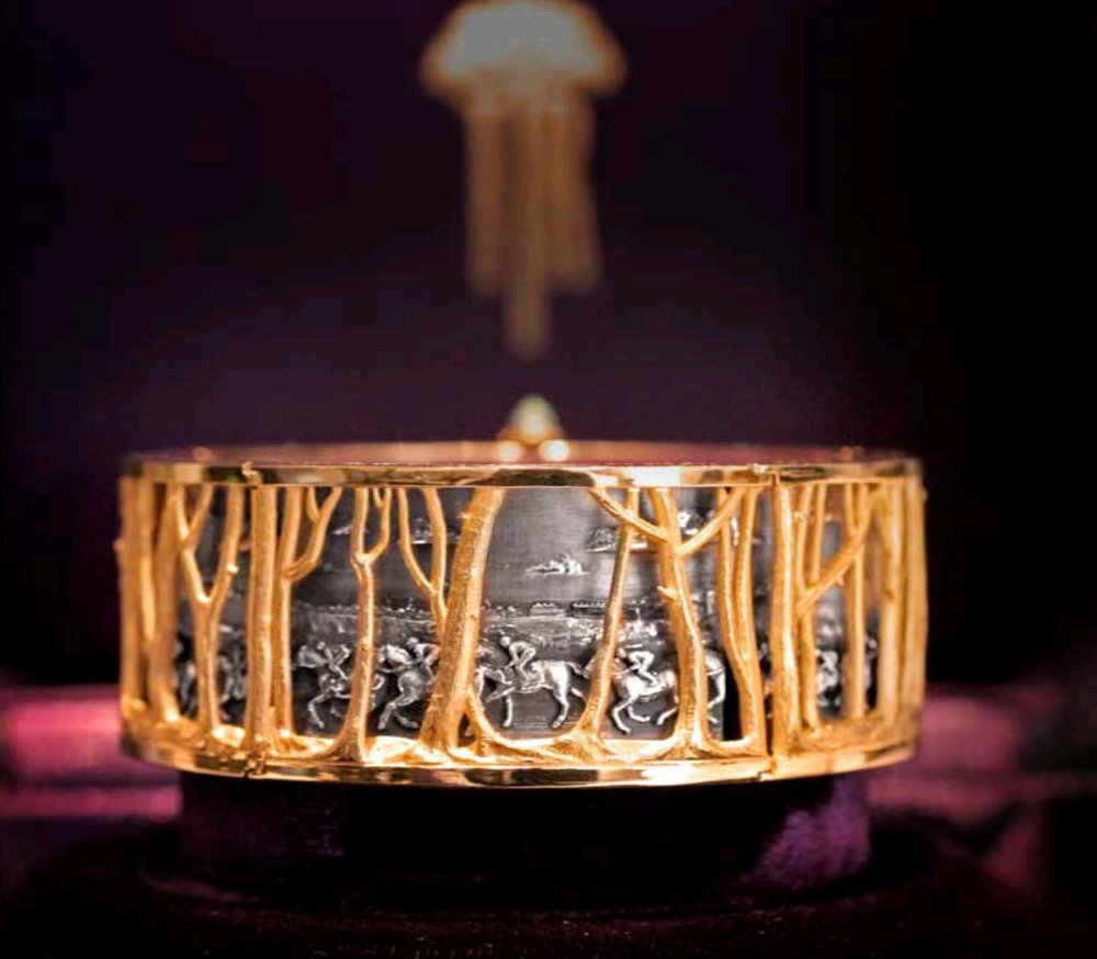 Gold, silver, diamonds and opal set bangle depicting horse racing at Goodwood, West Sussex, England.