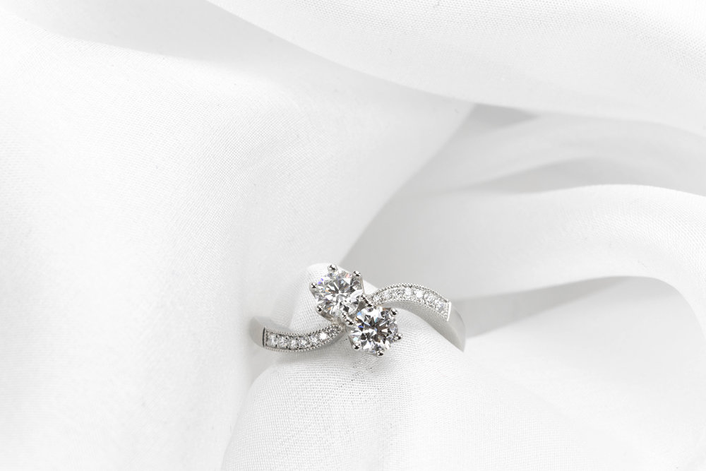 Platinum mounted diamond 2 stone crossover ring with grain set diamond shoulders. Made in Chichester, England.