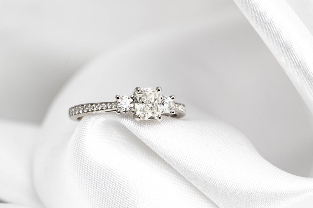 Platinum mounted cushion and round brilliant cut diamond 3 stone ring with diamond shoulders. Made in Chichester, England.