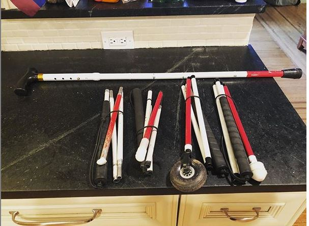 five white canes sit on a black counter