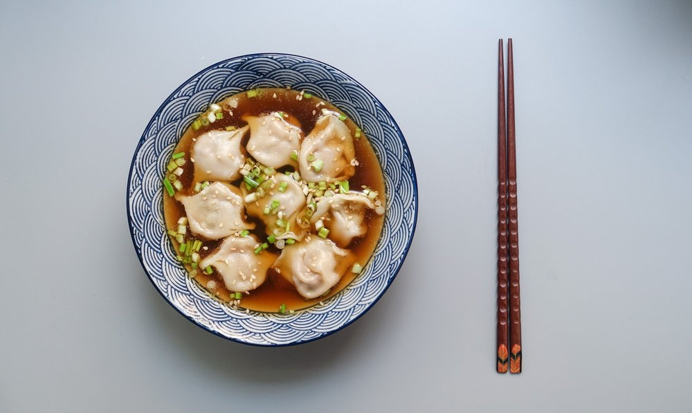 dumpling soup, garnished with scallions