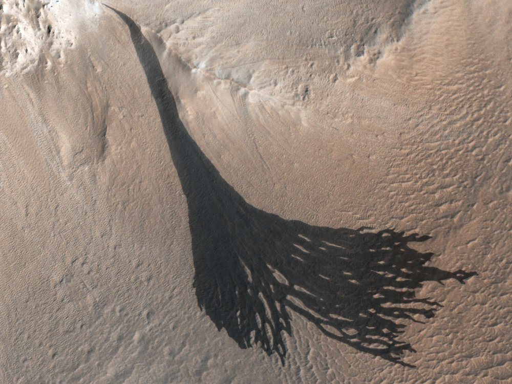 A splitting slope streak in the equatorial region of Mars. This streak formed at an elevation point and extends downhill. The slope streaks found on Mars often occur in regions of dusty regolith with low thermal inertia. The scientific community is divided over whether the slope streaks form via a wet or dry mechanism. Recent studies indicate that a wet mechanism may be responsible, although it could be through a combination of both a wet and dry mechanism. Image ID: ESP_053518_1955. Credit: NASA/JPL/University of Arizona