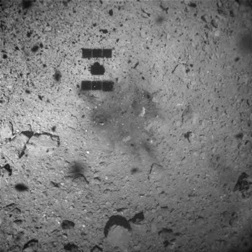 The touchdown zone after Hayabusa2 departed Ryugu's surface. The dark central area was discolored from Hayabusa2's thrusters or the impact bullet used to eject surface material. The sun is behind the spacecraft, therefore, Hayabusa2's shadow is clearly visible on the surface. Credit: JAXA, University of Tokyo, Kochi University, Rikkyo University, Nagoya University, Chiba Institute of Technology, Meiji University, University of Aizu, AIST.