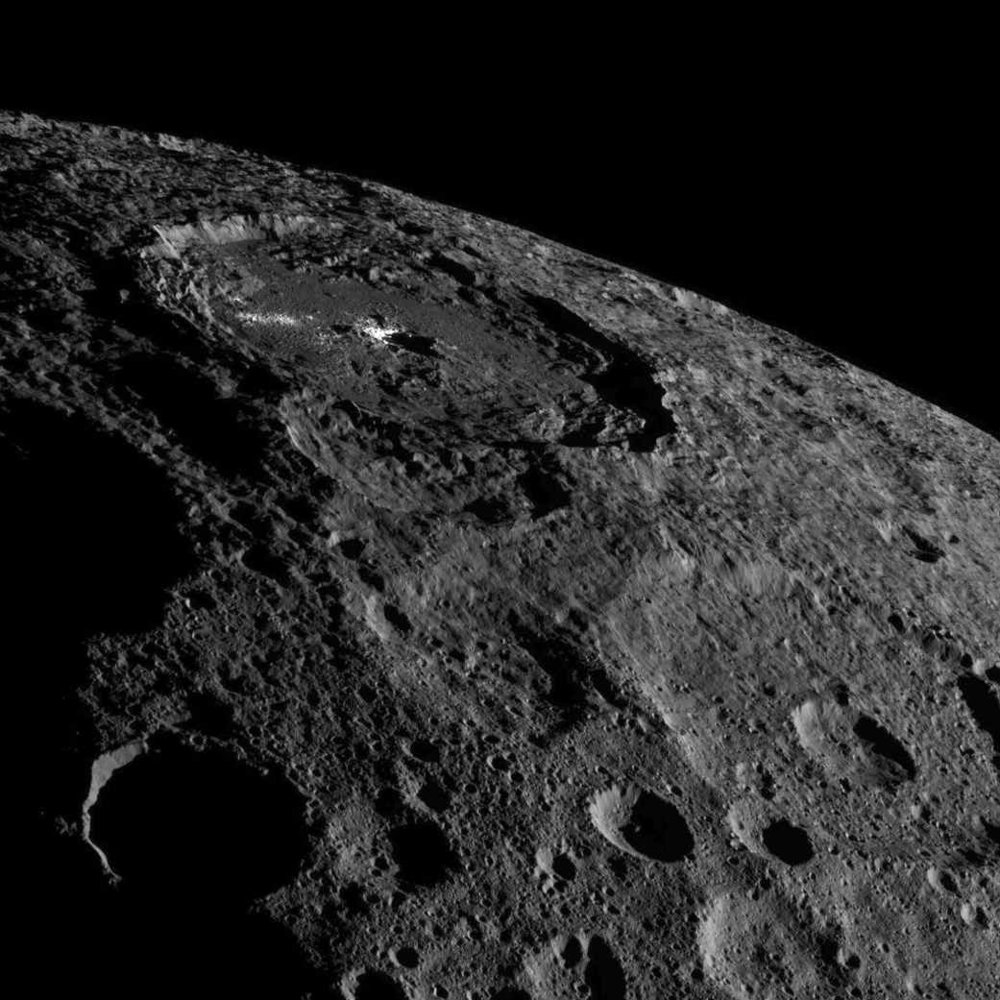 The Occator crater on asteroid Ceres. The NASA Dawn spacecraft identified ice within the top meter of the surface. Ice likely exists here because Ceres has a very low thermal inertia, small axial tilt, and a semi-major axis at 2.77 AU. Low temperatures help prevent ice sublimation. Credit: NASA/JPL-Caltech/UCLA/MPS/DLR/IDA.