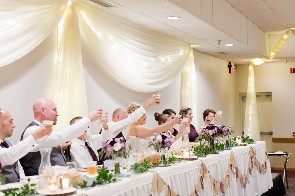 Lindsey White Photography   Cheers at the head table with white table skirting and ceiling draping as the backdrop   wedding venue in Minnesota ballroom