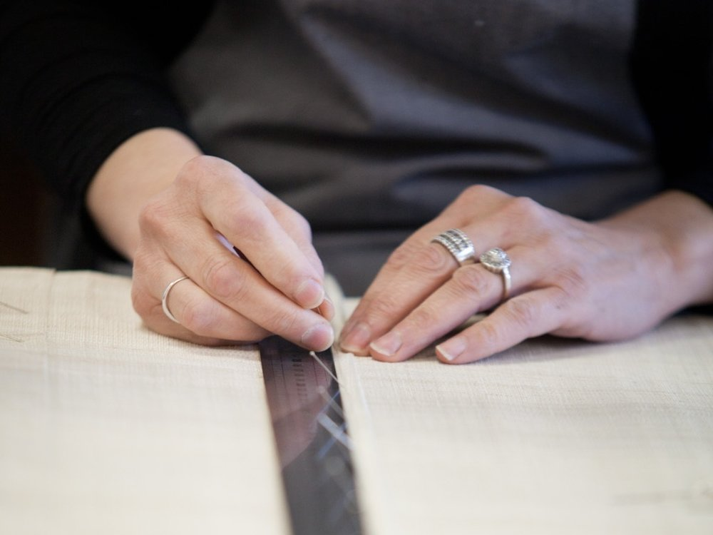 Stitching Trims by Hand - Rosettes, brocaded braid, knitted gimp, and bullion fringes… For more than thirty years, the men and women in Jouffre's workshops have crafted thousands of trims, handstitched to the very highest standards of workmanship.