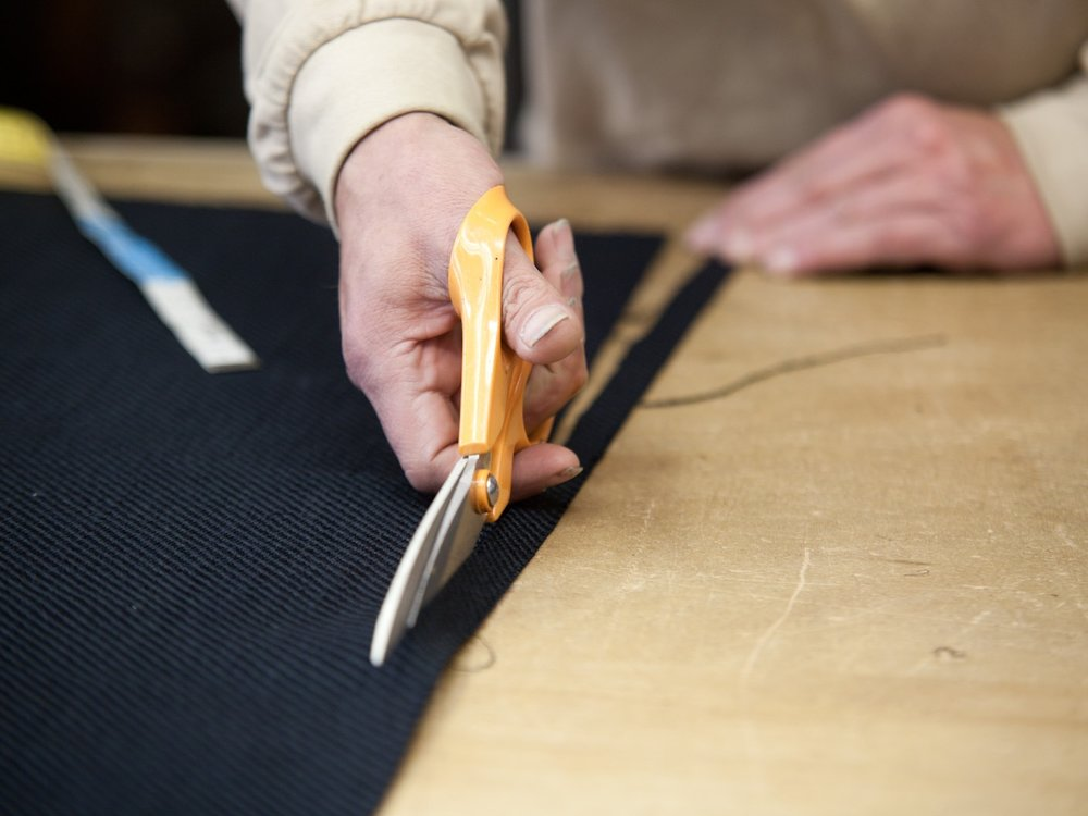 Cutting the Fabric - The pattern of a cover, or the complexity of a chair or sofa, means that fabric-cutting is a delicate operation. The upholsterers – equipped with a ruler and a pair of scissors, but primarily with their savoir-faire – devote themselves body and soul to this first perilous stage.
