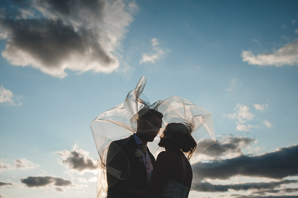 JMA-Photography-silhouetted-wedding-couple-under-flying-veil.jpg