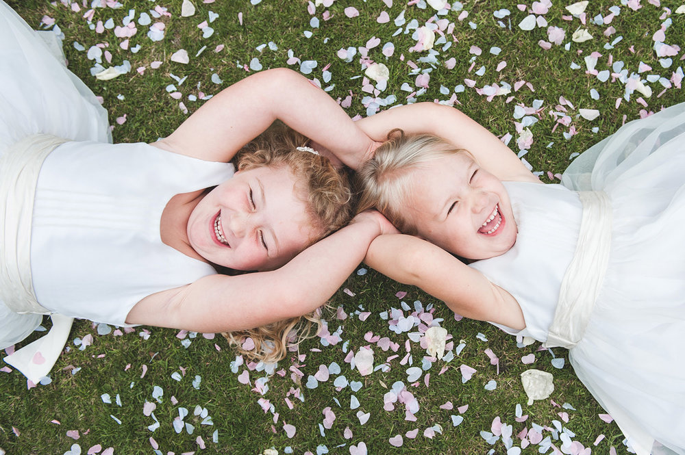 jma-photography-flowergirls-laying on-confetti-laughing.jpg