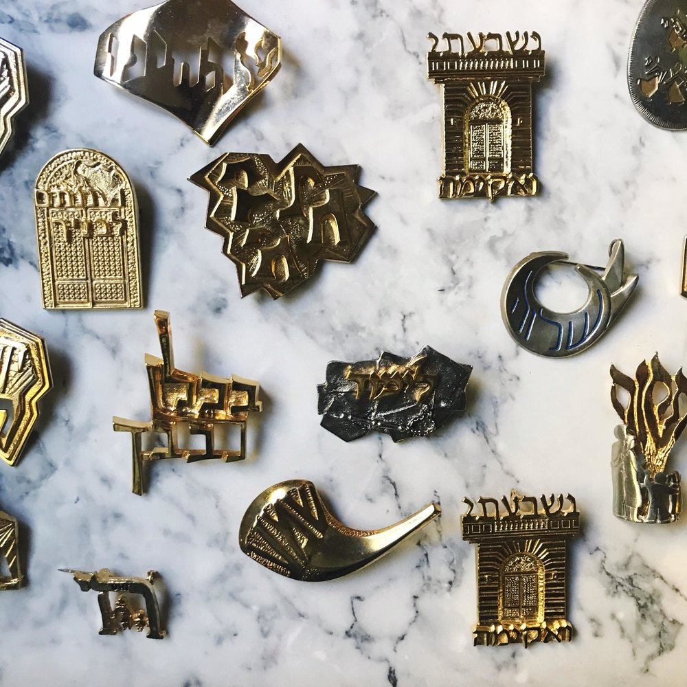 The walls of Adam Schwartz's living room are lined with Judaica. - Haggadahs are stacked on top of boxes of Hebrew alphabet costume jewelry. A handful of mezuzot are bundled next to menorahs from every design style.
