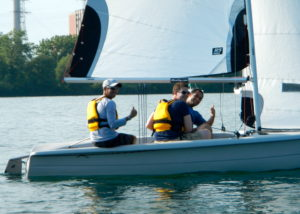 A group of three people sailing together in an RS Vision