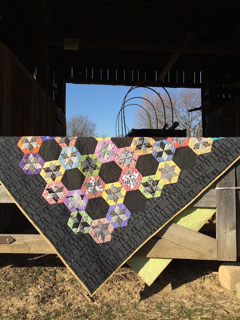 scrap quilt diamond English paper pieced blocks appliquéd onto a black background