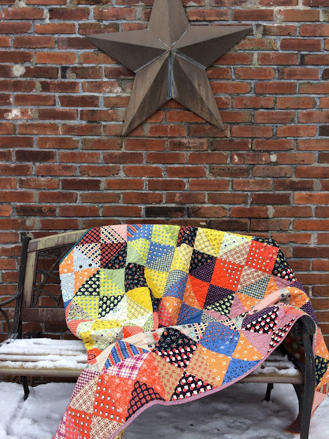 scrap quilt drapped on bench.jpeg