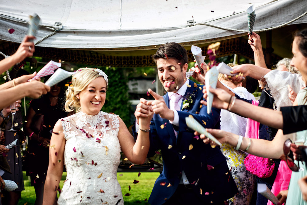 Ballyvolane House Wedding Photos by Cork and Kerry wedding photographer David Casey. Bride and Groom fun photos. Bride in White wedding dress and groom in navy suit with mint tie. Confetti photo