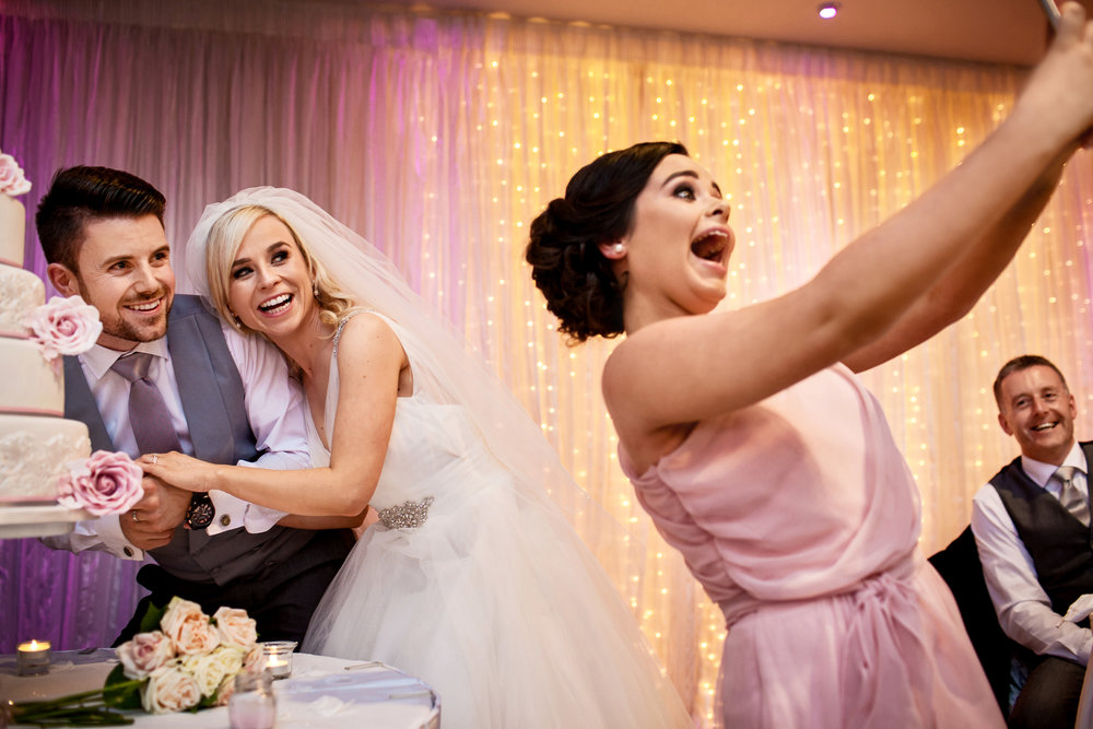 Fun wedding photography of selfie cutting the wedding cake. Great Southern wedding photography Kerry Ireland by Kerry wedding photographer David Casey