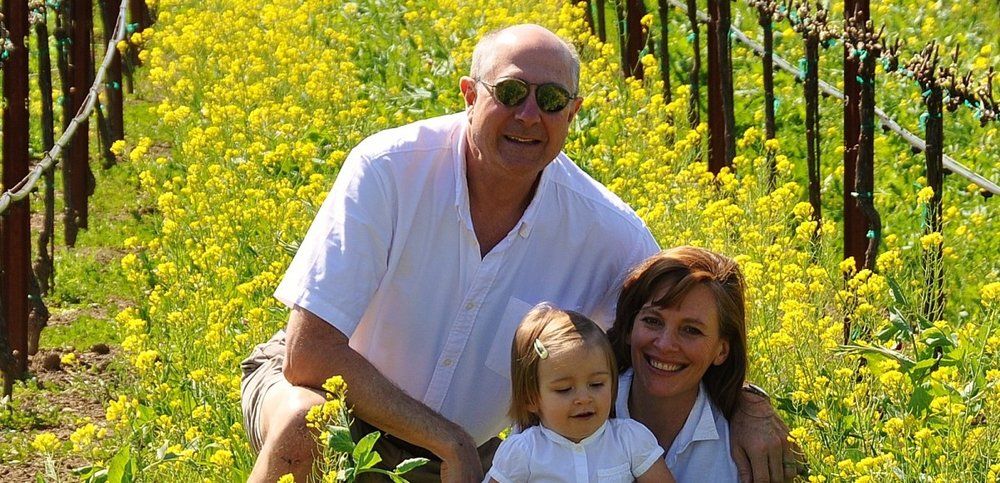 Guy, Sarah, and Ella surrounded by yellow flowers during springtime in the vineyard in Anderson Valley, Mendocino County's wine country