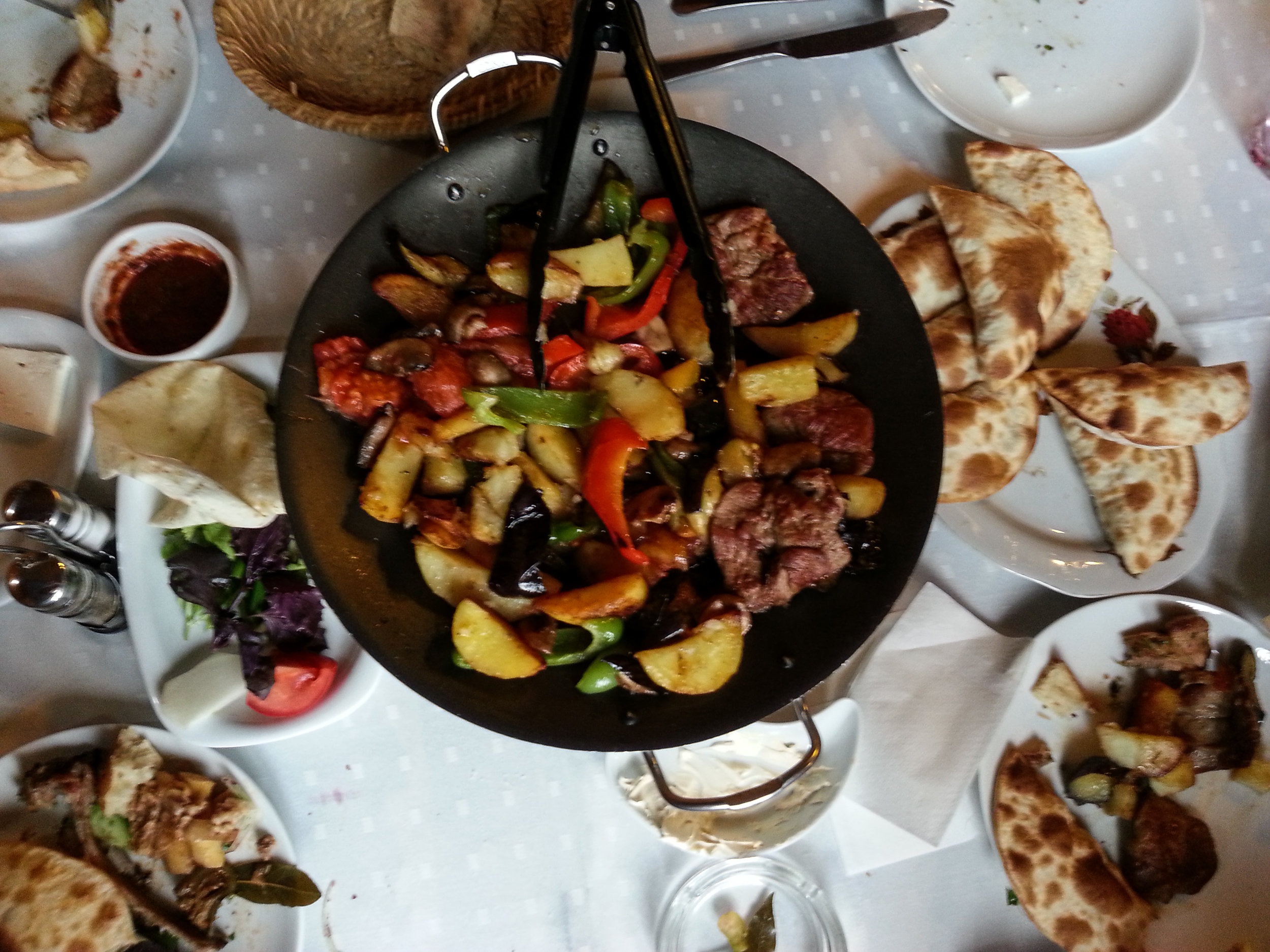 Meat fried with peppers and herbs and spices in a cast iron pan. On the side are some gutab (pastry filled with meat),