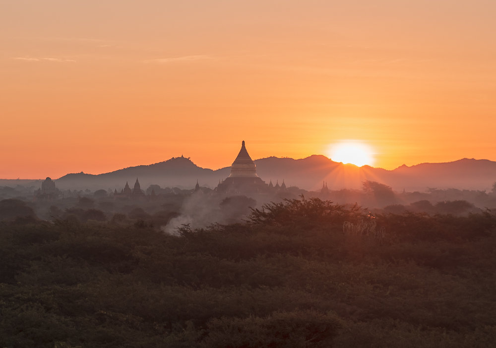 The sun peeks out over the hills surrounding Bagan