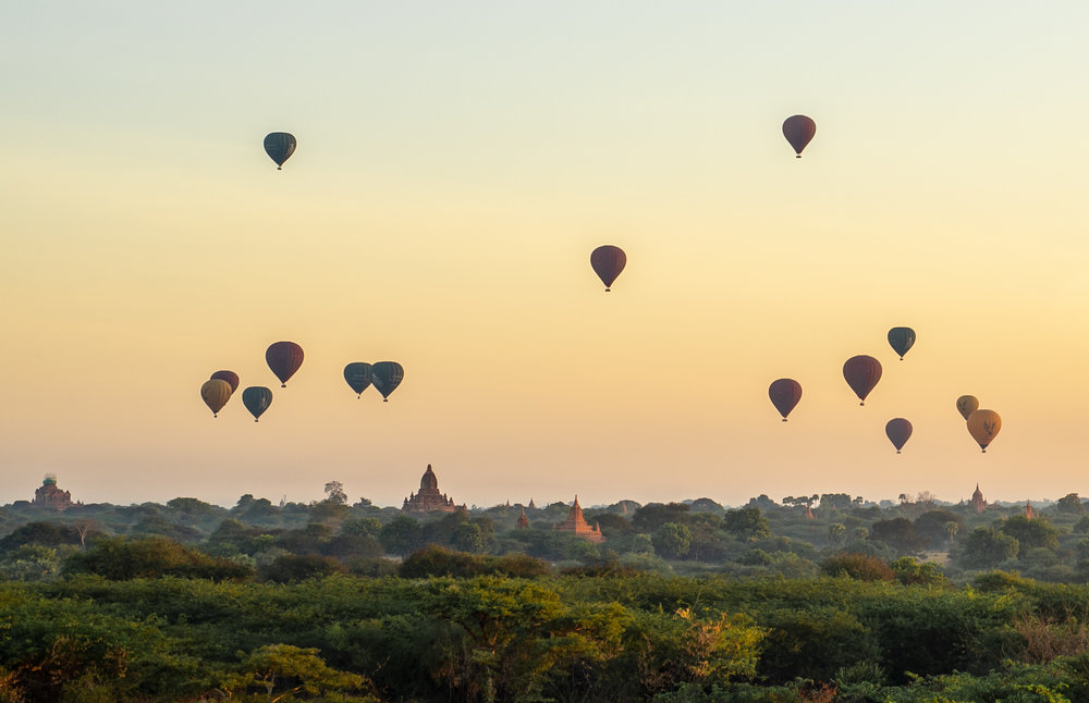 Hot air balloons fly over Bagan just after sunrise