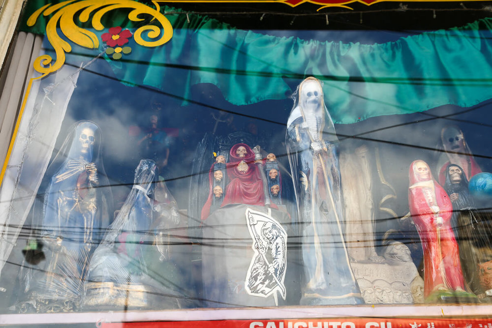 Argentina's Popular Saint Culture, San La Muerte statues in a store window