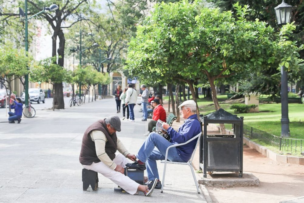A man gets his shoes shined in the main square in Salta