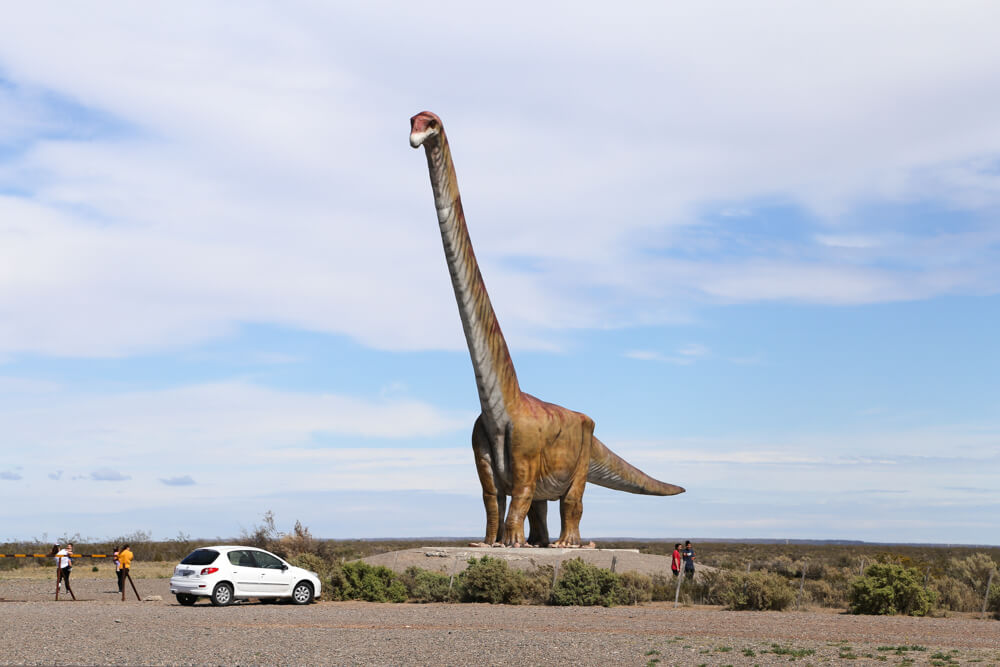 A large dinosaur statue on the side of the road in Trelew