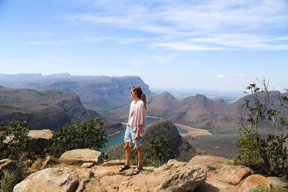 A woman standing on a cliff overlooking the Panorama Route on a road trip spending two weeks in South Africa