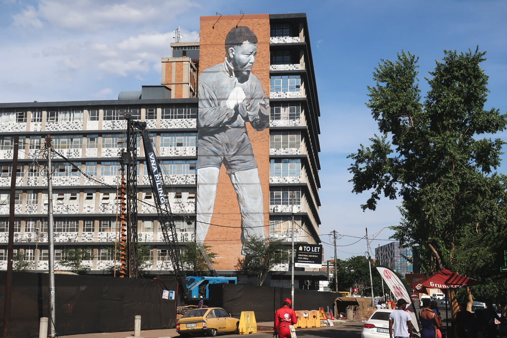 2 weeks South Africa itinerary starts in Johannesburg with this large Nelson Mandela mural on the side of an apartment building.